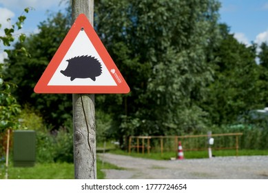 Elsfleth, Germany - July 16, 2020: small traffic sign with the outline of a hedgehog next to a gravel path, warning motorists that hedgehogs might cross the way