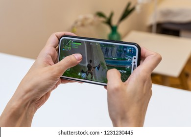 Elva, Estonia - November 15, 2018: girl is holding iphone with online Fortnite game on display, playing video game
