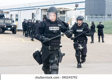 ELWOOD, ILLINOIS - OCTOBER 1, 2012: Riot police at the Walmart distribution center run up to striking warehouse workers and supporters as they rally for better wages and working conditions.