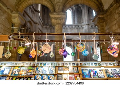 Ely, Cambridgeshire, UK - Circa November 2018: Shallow focus on some of glass babuls seen hanging within a souvenir shop within a famous English Cathedral. Religious books can be seen on display.