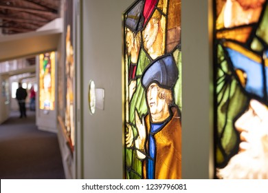 Ely, Cambridgeshire, UK - Circa November 2018: Shallow focus of very old, stained glass windows seen within an exhibition in a famous English cathedral.. Vistors can be seen in the background.