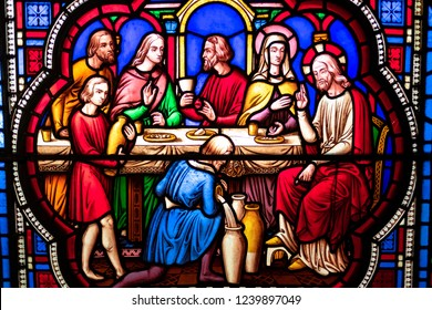 Ely, Cambridgeshire, UK - Circa November 2018: Fine detail of an historic stained glass window depicting Christ at the table with holy people. The glass dates back many hundreds of years.