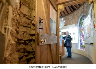 Ely, Cambridgeshire, UK - Circa November 2018: Detailed view of a wooden door at the entrance to a cathedral souvenir shop. Located in the ancient cathedral which accessed via a spiral stairwell.