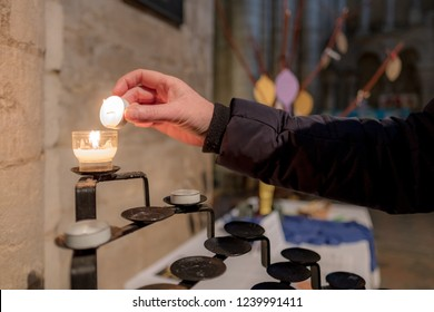 Ely, Cambridgeshire, UK - Circa November 2018: Woman seen lighting a tea light within the chapel of a famous, English cathedral. A small donation is required to purchase a tea light for lighting.