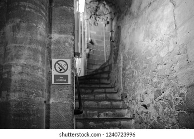 Ely, Cambridgeshire, UK - Circa November 2018: Detailed image of a very old stonework staircase leading to a cathedral's souvenir shop. A No Smoking sign can be seen attached to a supporting pillar.