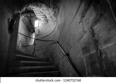 Ely, Cambridgeshire, UK - Circa November 2018: Dark and eerie scene of a very old, stone staircase within the confines of a cathedral. A handrail leading to a small, leaded window can be seen.
