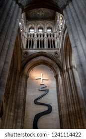 Ely, Cambridgeshire, UK - Circa November 2018: Detailed, interior view of a famous English Cathedral, showing its impressive architecture. A crucifix is illuminated, giving a heavenly effect.
