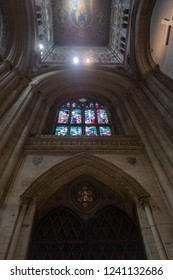 Ely, Cambridgeshire, UK - Circa November 2018: Vertical view of gothic stained glass window seen within a cathedral.  Giving a dark, atmospheric appearance, seen near the entrance.