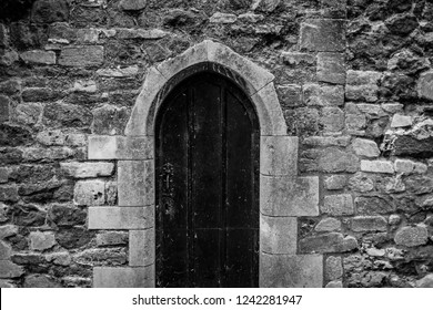 Ely, Cambridgeshire, UK - Circa November 2018: Detailed view of a locked, gothic styled wooden door seen within a very old, stone work wall. Historically, the wall is many hundreds of years old.