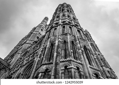 Ely, Cambridgeshire, UK - Circa November 2018: Vertical view of the impressive gothic-styled architecture of a famous English cathedral. Showing detail of the stonework, windows and unique tower.