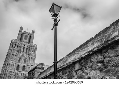 Ely, Cambridgeshire, UK - Circa November 2018: Street view of a famous English cathedral together with a wrought iron lamppost adjacent to a gothic styled stone wall, located to this famous landmark.