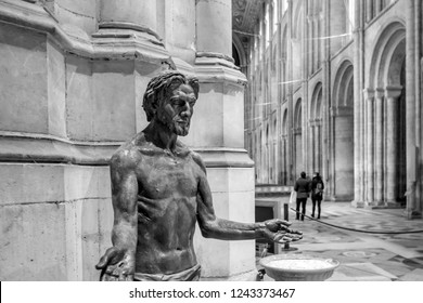 Ely, Cambridgeshire, UK - Circa November 2018: Large, statue of a man seen within a famous English Cathedral. The large interior design is visible, seen in scale against a distant couple of people.