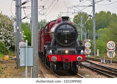 ELY, CAMBRIDGESHIRE, UK - MAY 18, 2013: Looking somewhat out of place amongst all the OLE and trackside paraphernalia, LMS Jubilee Class 4-6-0 No. 45699 'Galatea' eases over Bridge Road level crossing