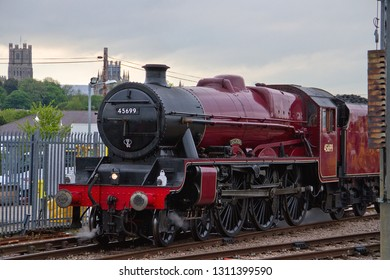 ELY, CAMBRIDGESHIRE, UK - MAY 18, 2013: With the city's cathedral just visible behind, LMS Jubilee Class 4-6-0 No. 45699 'Galatea' reverses into the sidings at Ely Station, about to take on water.