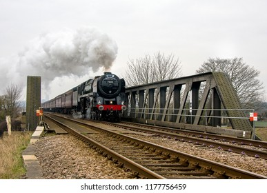 ELY, CAMBRIDGESHIRE,UK - MARCH 11, 2010: BR Britannia Class 4-6-2 No. 70013 Oliver Cromwell crosses the Great Ouse river bridge as it leaves Ely and the city's cathedral behind, heading for Norfolk.