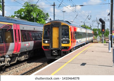 ELY, CAMBRIDGESHIRE/UK - May 23, 2019. East Midlands class 158 DMU pulls into platform 2 while a Cross Country class 170 'Turbostar' train stands in platform 1 at Ely, Cambridgeshire, England