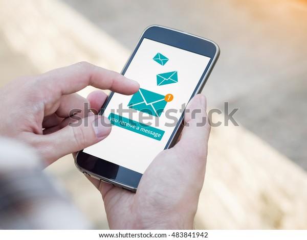 Aplicación de correo electrónico en la pantalla del teléfono inteligente. Recibes un mensaje, se recibe un mensaje nuevo. Mano del hombre sostiene un smartphone