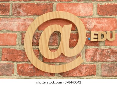 Email (Commercial At Symbol) dot EDU for Education hanging on brick wall