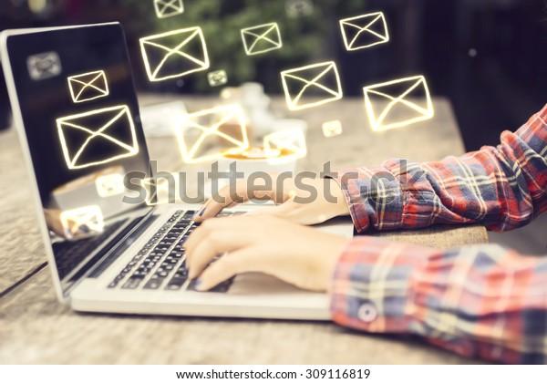 ノートパソコンの女の子の手を使ったEメールのコンセプト