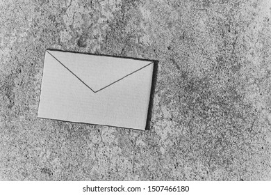 email envelope sign made of cardboard on concrete background, minimalistic shot in black and white with copyspace