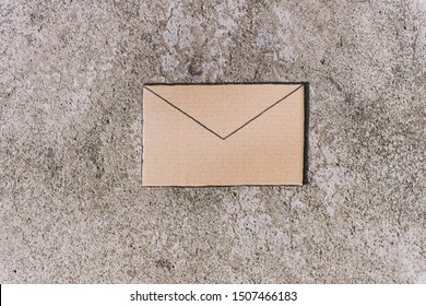 email envelope sign made of cardboard on concrete background, minimalistic shot with muted tones
