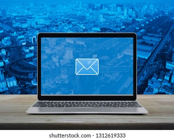 email flat icon with modern laptop computer on wooden table over city tower, street, expressway and skyscraper, Business contact us online concept