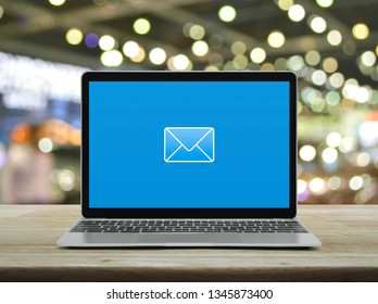 email flat icon with modern laptop computer on wooden table over blur light and shadow of shopping mall, Business contact us concept
