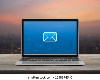email flat icon with modern laptop computer on wooden table over blur of cityscape on warm light sundown, Business contact us online concept
