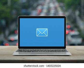 email flat icon with modern laptop computer on wooden table over blur of rush hour with cars and road in city, Business contact us online concept