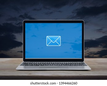 email flat icon on modern laptop computer screen on wooden table over sunset sky, Business contact us online concept