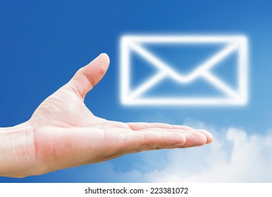 Email icon on hand and mail sybol icon clouds on blue sky