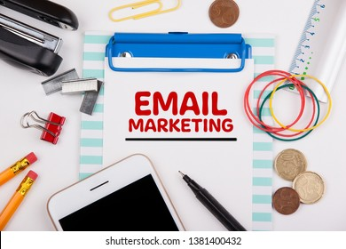 Email Marketing concept. Office desk with stationery and mobile phone