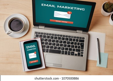 Email marketing concept on laptop and smartphone screen over wooden table. All screen content is designed by me. Flat lay