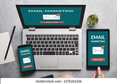 Email marketing concept on laptop, tablet and smartphone screen over gray table. Flat lay