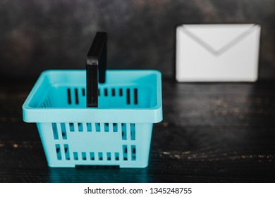 email marketing concept: shopping basket and email envelope next to it