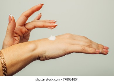 emale hands with a moisturiser on light background. Close-up of Woman Applying Cream on Hand. Hands Skin Care.