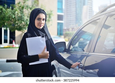 Emarati Arab Business woman getting inside the car in Dubai, United Arab Emirates.