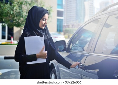 Emarati Arab Business woman getting inside the car in Dubai, United Arab Emirates.