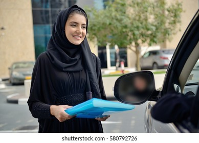 Emarati Arab Business women getting into the car in Dubai, United Arab Emirates.