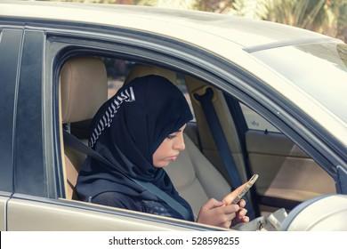 Emarati Arab woman in the car using smartphone, wearing Hijab and abaya