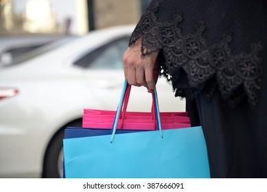 Emarati Arab woman coming out of shopping in Dubai, United Arab Emirates.