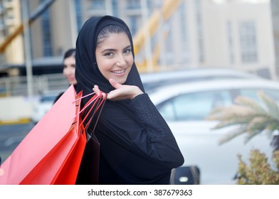 Emarati Arab woman coming out of shopping in Dubai, United Arab Emirates.