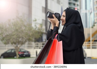 Emarati Arab woman coming out of shopping and taking photo with her camera in Dubai, United Arab Emirates.