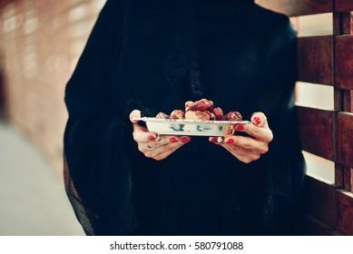 Emarati Arab woman holding dates plate, Dubai, United Arab Emirates.