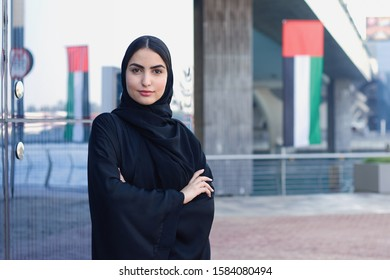Emarati Lady on Abaya, UAE girl with flag Emirates colors. Beautiful Arab woman on black dress in Dubai. Crossed arms of Arabian National with Uniterd Arab Emirates flag on the back
