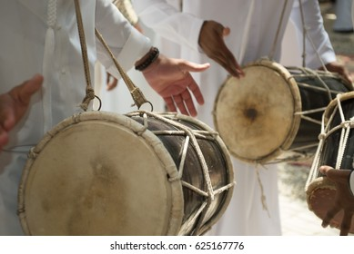 Emarati locals celebrating in their traditional way and dancing while playing their drums.
