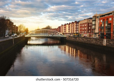 Embankment of Liffey River in Dublin, Ireland. Sunset view with buildings and city lights at the background