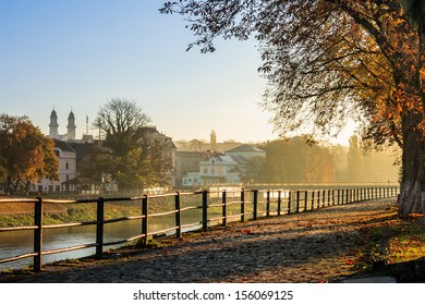 embankment of the old town strewn with foliage and filled with light on autumn morning