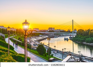 Embankment of the river with stairs and street lights at the summer sunset