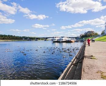 Embankment of the river Volga in Tver, Russia. Autumn Sunny day. Pleasure boats at the pier. Wild Mallard ducks swim in the river. The new Volga bridge. People walk along the promenade.